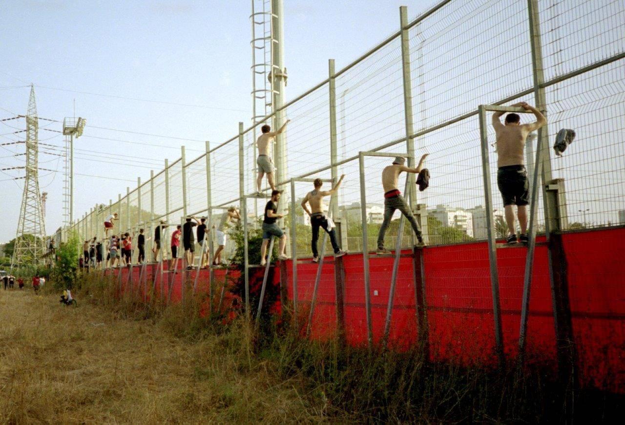 אוהדי הפועל תל אביב צופים באימון מבעד לגדר